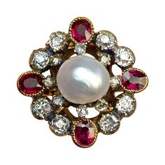 Antique Pearl Ruby Diamond Renaissance Revival Ring, circa 1880  The ring features a natural 8.4 mm salt water pearl in an openwork silver topped 18Kt gold bezel. The pearl is surrounded by two rows of gemstones: eight rose cut diamonds, eight old mine diamonds and four rubies. Approximate total diamond weight is 1 ct.