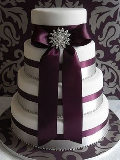 Pastel de boda del ciruelo con la cinta centrada en cada nivel