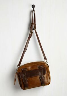 On business trips and family vacations alike, this reliable bag is always swinging by your side! In a cognac hue with a brown flap, decorative buckles, and a detachable strap, this vegan faux-leather purse is conveniently chic for both work and play.