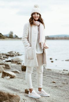 The Best Outfit Ideas Of The Week: Fashion blogger 'Lovely Pepa' wearing a white beanie, a white coat, cream skinny jeans, a grey sweater, beige suede sneakers and a blush mini bag. Winter outfit, cozy outfit, coat outfit, sneakers outfit, casual outfit, comfy outfit, travel outfit, winter layers, all white outfit, neutral tone outfit, neutral layers outfit, winter trends 2016.