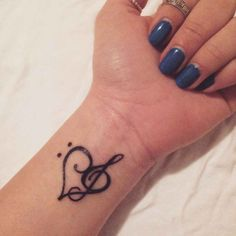 Little wrist tattoo of a bass clef and a treble clef creating a heart on Nancy.