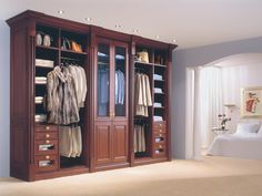 Timeless, custom cabinetry with full-height storage neatly displays his and her belongings. This closet system, designed by Studio Becker, is made from Mahogany and can easily pass for a fine antique.