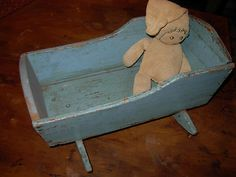 For Christmas one year my father made me a doll cradle from wooden crate boxes, painted it robins egg blue, and placed stencils on the sides.  I still have it and it very similar to this picture.