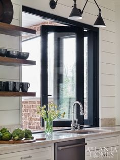 A kitchen window slides open as a pass-through to the outdoor dining space, next to open shelving with everyday dinnerware.