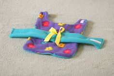 This adorable small coat is sweet and sassy. Purple flower fleece is lined in a plush teal fleece and a soft teal fleece belt. There is a yellow bow on the belt complete with a purple rosette for an elegant little girl.