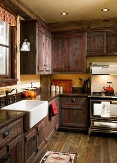 I love the rustic cabinets and big farm sink…also the stove and the sconce on the end cabinet.