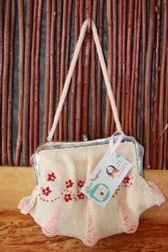 """The perfect accessory for your night out.  Handmade with ivory pink beads, antique white pearl cotton thread and ruby red embroidered flowers.  The inside is lined with a pink linen.  This purse measures 9"""" x 6"""" with a 14"""" beaded strap held together by a metal purse frame.  This purse is sure to capture attention."""