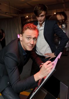 Pin for Later: Take a Moment to Appreciate Tom Hiddleston's Hottest Moments  He signed a book while Douglas Booth kept watch.