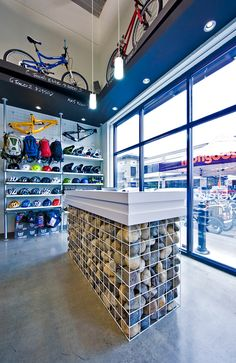 A contemporary bicycle shop; retail design by Hatch Interior Design Inc. in Kelowna, BC.  Innovative rock gabion style reception desk.