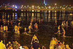 hindu pilgrims bathing in the ganges river at sangam at night - kumbh mela 2013 (india), bath, crowd, fence, ganga, ganga river, hinduism, holy bath, holy dip, kumbha mela, maha kumbh, maha kumbh mela, men, paush purnima, people, reflections, ritual bath, river bath, river bathing, street lights, triveni sangam, water, women, yatris
