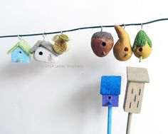 Birdhouses, mason bee tubes and butterfly houses made from air dry clay and wood in dollhouse scale
