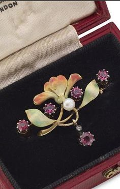 An Art Nouveau enamel brooch Of stylised floral design, set centrally with a pearl with two circular-cut garnets to each side, to a drop pendant set with a similarly-cut garnet with diamond accent, width 36mm, bearing Austro-Hungarian import control marks, pearls untested, to a fitted case retailed by Mallett, London