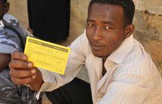 Un homme montre son certificat de vaccination contre la fièvre jaune