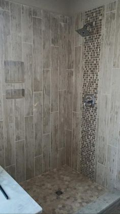 """Shabby Chic"" Rustic wood looking tile with floor to ceiling vertical deco panel. Old navy Bianco with Clio Hera mosaic as deck panel. Multi textured hexagon mosaic on floor."