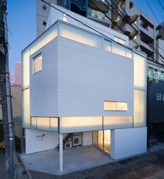 Translucent windows create a glowing frame around the facade of this Tokyo townhouse when the lights are turned on inside. Designed by Japanese studio Yoritaka Hayashi Architects, House in Nakameguro has four storeys but is the same height as surrounding three storey residences. Plywood lines the interior walls of the two middle floors, which include