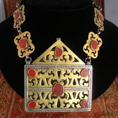 Turkmenistan | Antique old silver guilt Turkomen Prayer Box Necklace from the Tekke Tribe; good silver alloy, fire gilded and embellished with carnelian stones. | ca. second half of the 20th century | Reserved.