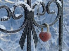 Heart lock on a snowy iron gate.