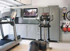 Garage home gym. Like positioning of machines, TV and storage (as well as how they mounted other storage on the wall to keep floors clutter free.  Cool to have all sports things together.