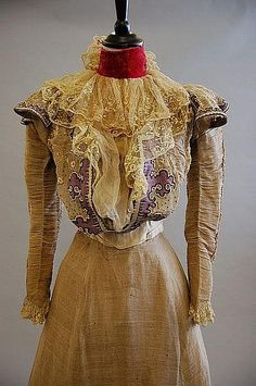 A rare Maison Worth summer gown, 1897, labelled and numbered 91416, with blue art-nouveau stamp to the ivory petersham waistband, the bodice and skirt of ecru silk organza spangled with gold sequins, edged with lilac felt and embroidered in white cotton with delicate trailing blooms, the bodice back fastened with flounced shoulders, ivory satin waistband and collar (later added crimson velvet neck-band), the front of the bodice with curved pouch inset with chiffon and lace jabot, tightly…