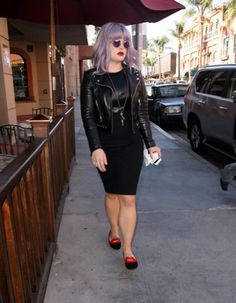 Kelly Osbourne is cool in a black leather jacket, red shoes and reflective purple sunglasses.