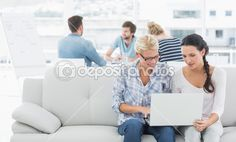 Women using laptop with colleagues in background at creative off — Stock Image #39201007
