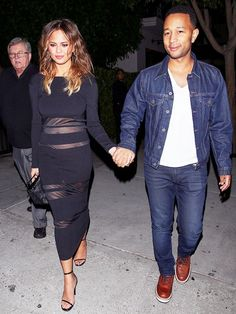 Chrissy Teigen wears a Self-Portrait Long-Sleeve Mesh-Trim Midi Dress and Saint Laurent Jane Leather Sandals.