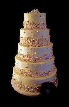 gold wedding cake with purple and pink flowers | pearl wedding cake is adorned with a gumpaste purple flower. The cake ...