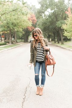 cute fall outfit idea, how to wear a green military jacket styled with black and white stripes,cognac booties and brown leather sole society bag, black and white stripes and utility jacket and coganc booties and brown bag