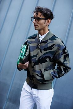 Pair an olive camo bomber jacket with white chinos for a laid-back yet fashion-forward outfit.   Shop this look on Lookastic: https://lookastic.com/men/looks/olive-bomber-jacket-white-dress-shirt-white-chinos-green-zip-pouch/12777   — White Dress Shirt  — Green Leather Zip Pouch  — White Chinos  — Olive Camouflage Bomber Jacket