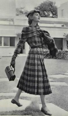 1955 Dior  Une veste très courte, en écossais  , est ceinturée de daim marron. La taille est bien marquée. La jupe plissée est d'une harmonieuse ampleur. Une large écharpe de même tissu enveloppe le buste, évoquant le tartan des highlan