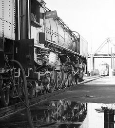 Union Pacific steam locomotive # 8444, is providing a reflection in a puddle at the railroad yard in Denver, Colorado, during 1980