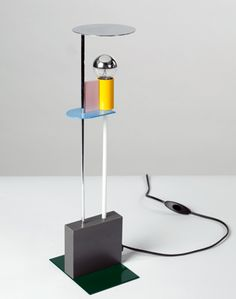 Piccadilly Gerard Taylor 1982 Materials Metal|Wood|Laminates  Dimensions (mm) Height	 445 Width	 110 Depth	  Description Table lamp composed of elements in laminated wood, painted and chromed metal | Produced by Memphis/Milano