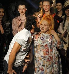 Designer Vivienne Westwood, surrounded by her models, is kissed on the cheek by her husband Andreas Kronthaler after displaying her 2013 fashion collection during Paris Fashion week