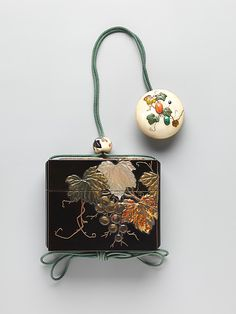 Case (Inrô ) with Design of Grapevine Period: Edo period (1615–1868) Date: 18th–19th century Culture: Japan Medium: Case: gold and colored lacquer and gold foil on black lacquer with greenstained ivory, mother-of-pearl, amber, and horn inlays; Fastener (ojime): ivory with design of plants; Toggle (netsuke): ivory medallion carved with design of fruited vines