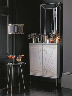 Inspired by Art Deco styling the drinks cabinet has fully fold out doors with storage for bottles and glasses.