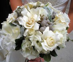 All things white and platinum ....  fragrant gardenias, feathery lisianthus, ivory roses, silver brunia berries and velvety soft dusty miller in the bridal bouquet. The groom's boutonniere was a simple cluster of silver brunia berries finished with a platinum satin ribbon wrapped around the stems.