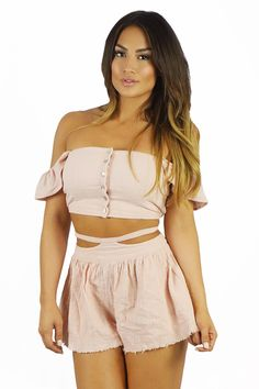 """Spring vibes all day long in this soft pink button down two piece set by Somedays Lovin. Wear this fitted top with ruffle sleeves on or shrug the to the side for an off the shoulder crop top look. Strappy high waisted short bottoms sit comfortably right below your belly button. The gathering along the flowy shorts waistline creates a flared """"skirt like"""" look.  #pinktwopiece"""