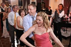 A lovely bridesmaid in a gathered, rose-colored strapless gown and a pearl necklace leads a dance train around the floor while John Parker and the John Parker band delight the wedding's guests with music for the party, held at the The University Club on the campus of the University of Pittsburgh.  http://www.jpband.com/weddings.html