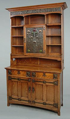"Oak Bookcase with Repoussé Copper and Enamel Panels with an inscription ""Vita Sine Literis Mors Est"" (A life without learning is death, J Johnson Pettigrew). Shapland and Petter, based in Barnstaple in Devon produced some of the finest examples of decorative 'artistic' furniture in the Arts and Crafts style."