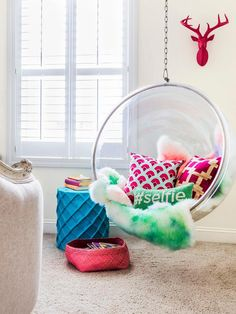 Chic teen girl& room features a pink decorative deer head over an acrylic hanging bubble chair, Candelabra Home Bolo Chair, lined with pink and green pillows next to a blue stool table, Stray Dog Designs Net Stool.