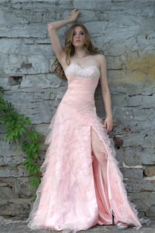Sexy blush strapless long prom dress. Embellished bodice has sweetheart neckline and shirred empire waist, cascading ruffles overlay blush skirt offers beaded trim and slit accent.
