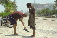 homem que dá seus sapatos para uma menina de rua de pés descalços.