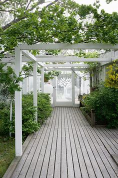 Modern white pergola covering a wooden deck.