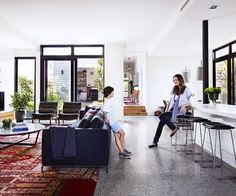 Open-plan kitchen and living: dark grey polished concrete floor, thick black window frames, black leather padded bar stools