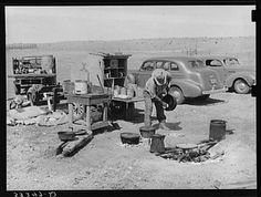 Camp cook at work with chuck wagon in center and truck for carrying bed rolls at left. Cattle ranch near Marfa, Texas