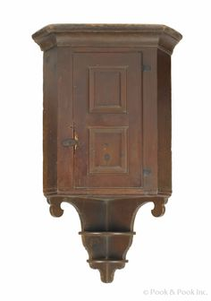 Realized Price: 52,140.00  Berks County, Pennsylvania pine hanging corner cupboard, ca. 1790, with a double raised panel door and scalloped two-tier drop, inscribed on inside of door, From Eshelman family, Oley Valley PA, 55 1/2 h., 27 1/2 w. Provenance: Sothebys David Wheatcroft, 1997