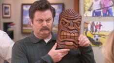 Ron Swanson (Nick Offerman) and his lookalike tiki gift on Parks and Recreation. Parks N Rec, Parks And Recreation, Pyramid Of Greatness, Tom Haverford, April Ludgate, Tiki Head, Nick Offerman, Parks Department, Leslie Knope