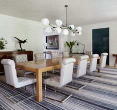 ALindsey Adelmanchandelier hangs above a custom cerused-oak Parsons table in the dining room. Vintage Arthur Lerod chairs sit atop a hand-knotted wool rug bySacco Carpet; a French Art Deco sideboard by Charles Dudouyt fromR.E. Steeleis topped with a sculpture by Gudmar Olovson.   Architectural Digest