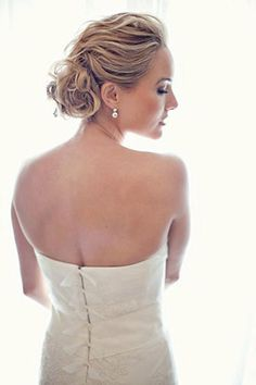 The tousled chignon from Southern Weddings is whimsical and sweet. With height in the front and twists into the low bun in the back, hairdressers of any skill set can perfect this look—and it's doable with any hair texture.