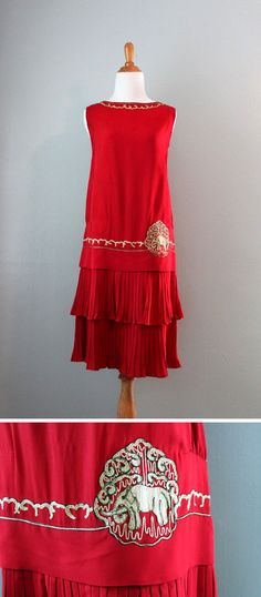 Dress ca. 1920s. Heavy red silk crepe or early rayon. Dropped waist over pleated, double flounced skirt. Neckline and waist trimmed with embroidery in off-white with metallic bronze trim. An elephant on one side of waist. Bodice lined in silk. HolliePoint/etsy